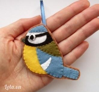 Hoặc bạn khâu một đoạn ruy băng nhỏ, ngắn vào đầu chú chim nhỏ này để làm móc treo chìa khóa. Bạn có thể làm hình hai chú chim đối xứng nhau rồi dán úp mặt trái vào nhau, phần ruy băng được dính ở giữa hai lớp dạ nền và nằm phía trên đầu chim.