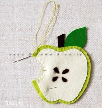 Khâu viền xung quanh quả táo xanh nữa là xong nhé! Lúc này phần cuống và lá đã được kẹp phía bên trong 2 miếng vải hình quả táo màu xanh rồi nên không còn lộ ra nữa.