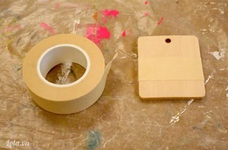 Miếng gỗ đục lỗ nhỏ trên đầu, rồi dùng băng keo dán ở giữa khung