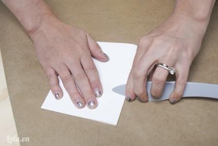 Giấy in A4 bạn gập đôi giấy lại, dùng một cái dao nhựa hoặc một cây thước vuốt cho giấy nằm xuống