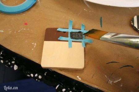 Dán một miếng băng keo bên trái của gỗ rồi dùng màu sơn đen sơn phủ lên. Đợi khô