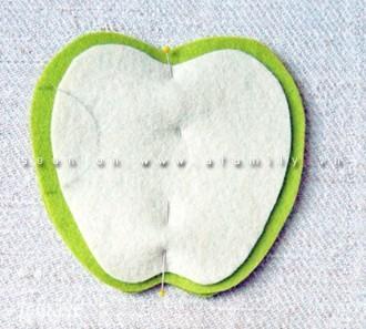 Đặt 1 miếng vải hình quả táo xanh ở dưới rồi đặt miếng vải hình quả táo trắng lên trên, dùng ghim nút giữ cố định. Vẽ vòng cung nhỏ trên quả táo.