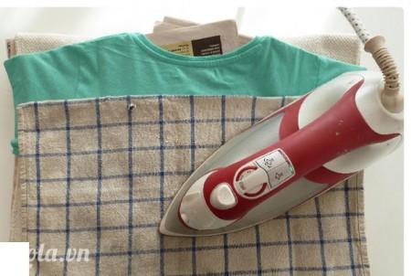 Dùng một cái khăn phủ lên trên mặt rồi dùng bàn ủi, ủi qua lớp bút chì sáp đó