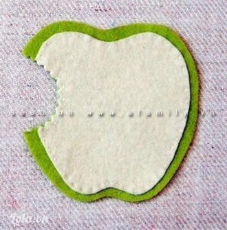 Khâu viền sát mép quả táo trắng. Vải dạ khá dày nên bạn có thể khâu viền quả táo trắng và đính nó vào quả táo xanh mà không bị lộ đường chỉ xuống mặt sau của quả táo xanh.