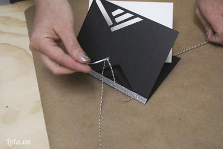 Xỏ kim chỉ qua 2 tờ giấy như hình, giữ lại một đoạn chỉ để tí cột làm mối nối