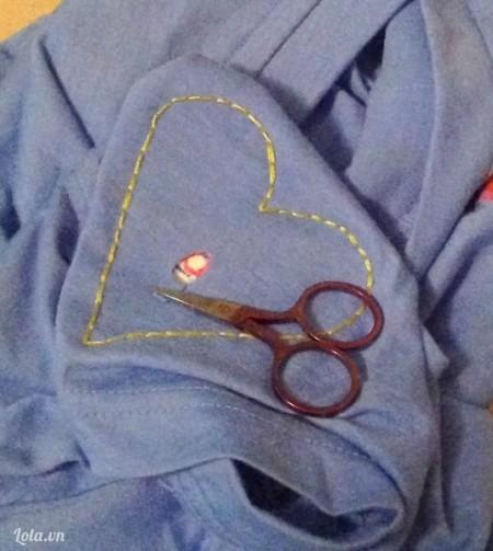 Lúc này thì mẫu hình trái tim nằm ở phía dưới cánh tay áo, cho nên ta sẽ lấy kéo cắt bỏ lớp vải của áo ra