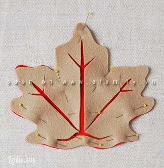 Đặt chiếc lá màu nhạt đã được cắt gân chồng xếp lên chiếc lá màu đậm. Điều chỉnh lại cho hai lớp lá vừa vặn thì dùng ghim nút đính tạm lại.