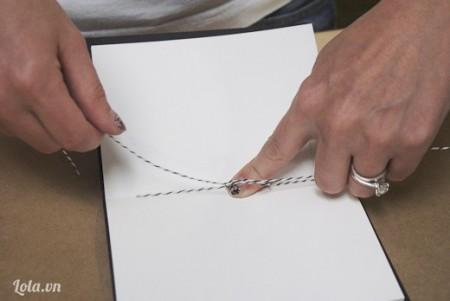 Làm tương tự khi xỏ kim qua lỗ còn lại, buộc mối nối giữa 2 tờ giấy