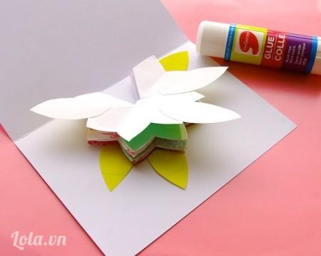 Dán chồng các hoa 7 cánh lại với nhau tại vị trí trung tâm lên trên tấm thiệp bên trong trang trí thêm các lá hoa
