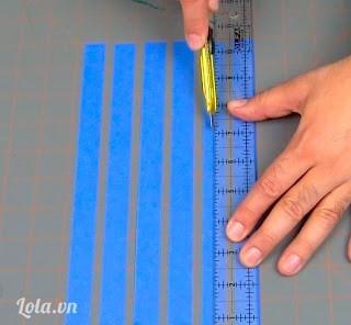 Dùng thước và dao rọc giấy cắt ra phân nữa