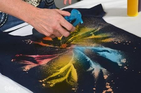 Pha nữa phần nước và nữa phần màu vào cái lọ phun rồi phun vào vị trí đã tẩy trên áo, theo chiều 6h và 9 h