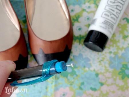 Lấy một tâm bông gắn vào bên dưới của bút bi, chấm tí mực trắng rồi chấm lên đôi giày để làm mắt cho chú mèo
