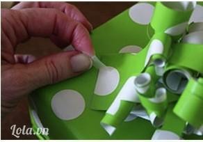 Dán lên trên hộp quà bằng keo, chỉnh sửa lại cho chỗ giấy này giống như một hình hoa bung nhé
