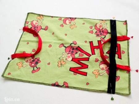 Đặt chồng miếng vải bìa lên trên miếng vải 1 rồi cho hai dây đeo lên hai bên