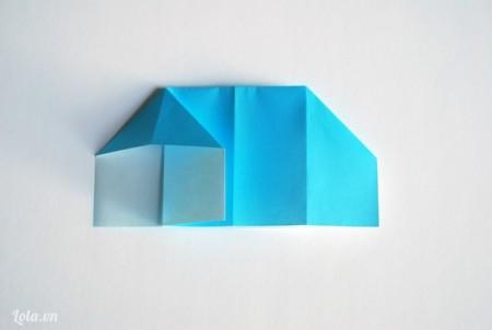 Bẻ một bên góc giấy ra phía trước tạo thành hình tam giác ngược lại
