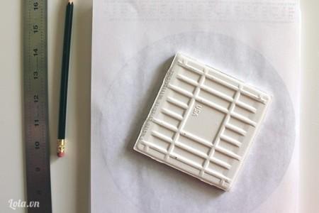 Đặt miếng gạch lên trên tấm giấy đã in sẵn hình cung hoàng đạo, dùng bút, thước vẽ hình vuông lên trên giấy