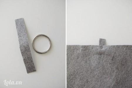 Cắt một tấm vải khác kích thước 1,5 cmx5 cm , xỏ vào khoen tròn và đặt nằm giữa hai miếng vải, khoảng 11,5 cm tính từ mép bên trái