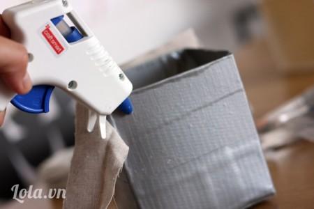 Dùng súng bắn keo dán các miếng vải dọc xung quanh hộp giấy