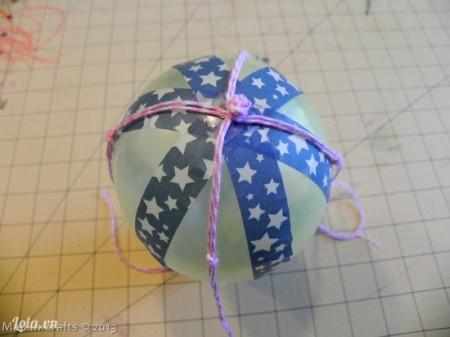 Trang trí bóng với băng keo washi,đặt dây lên trên bóng, chỗ nút thắc gút sẽ nằm trên đầu của quả bóng và chia đều dây ra thành 4 như ban đầu