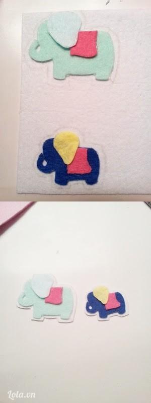Đặt hình chú voi lên trên tấm vải nỉ màu trắng, vẽ hình chú voi xung quanh rồi cắt ra làm nền