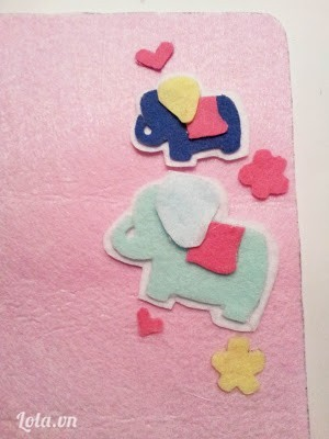 May chú voi dính lên trên mặt vải túi bằng chỉ trắng. Dán hình trái tim hoa lên trên bằng súng bắn keo