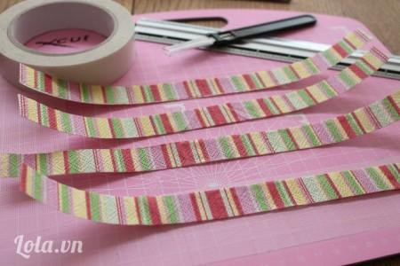 Làm các bảng lề cho các miếng giấy. Dán ruy băng lên bên trên và dưới của tờ giấy. Nếu không có ruy băng thì bạn có thể dùng băng keo 2 mặt, dán lên trên mặt vải, giấy mà bạn thích rồi dán lên trên các miếng giấy cứng