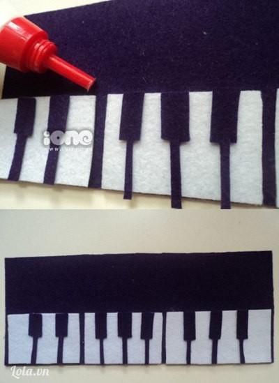 Mặt trước hộp bút các ấy cắt các phím đàn bằng vải dạ màu trắng và vải tối rồi dán chắc bằng keo sữa, để yên cho khô chừng 5 phút nhé.