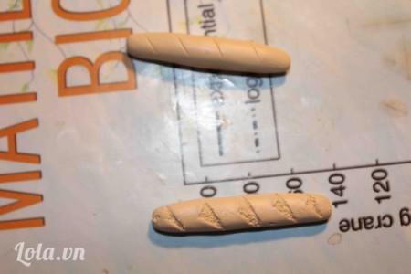 Sau đó cán ra thành hình ổ bánh mì mini như thến này, dùng dao tỉa xéo quanh thân bánh mì