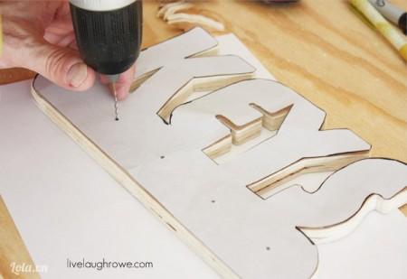 Đặt tờ giấy ngược lại lên trên gỗ để khoan lỗ gắn móc treo vào