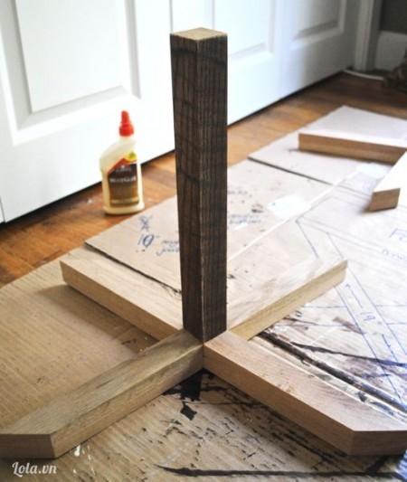 Đặt chân ghế chữ X lên trên sàn nhà. cho keo ở giữa và đặt một thanh gỗ trung tâm lên trên. Đợi khô 60 phút