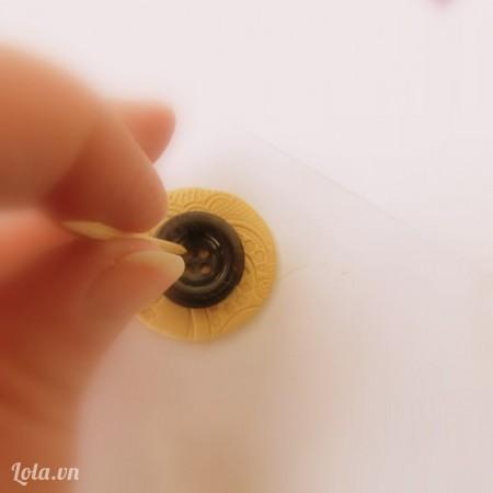 Đặt một nút áo lên giữa phần đất sét. Không ấn nút áo này nhé. Bạn sẽ lấy tăm tre đâm 4 lỗ tròn xung quanh nút áo