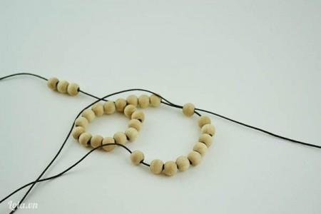 Lấy cuối sợi dây bên phải xỏ vào hạt cuối cùng của 10 hạt gỗ