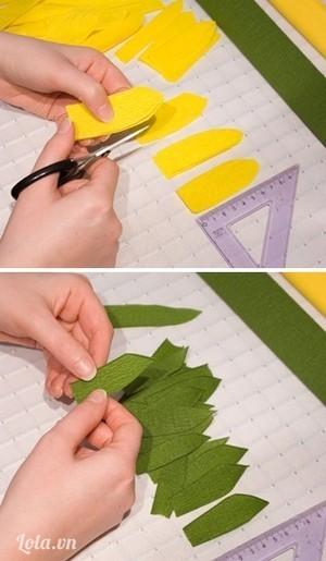 Cắt giấy vàng có kt 3cm x 7,5cm thành hình cánh hoa. Dùng tay vê nhẹ đường viền của cánh hoa, làm tương tự để có được những cánh hoa màu xanh lá cùng kích cỡ.