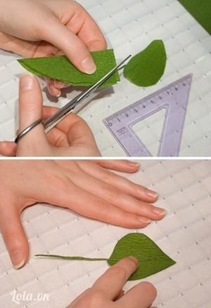 Cắt 6 miếng giấy xanh có kt 6cm x 8,5 cm thành hình lá, vê nhẹ đường viền xung quanh.Cắt dây kẽm dài khoảng 8,5cm, cuốn giấy kín thân kẽm, dán keo 1 đầu dây kẽm dài khoảng 3cm.Đặt phần dây kẽm đã dán keo lên trên chiếc lá và gắn vào chính giữa, làm tương tự để được 6 chiếc lá.