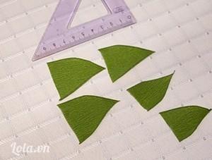 Cắt 6 miếng giấy xanh hình tam giác cân có kích thước mỗi cạnh 5cm, vê đường viền 2 bên để tạo thành hình nửa chiếc lá, đây sẽ là các mày lá nằm bọc dưới cuống mỗi lá.