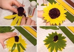 Dùng keo dán gắn 10 cánh hoa màu vàng quanh nhụy hoa dưới mép dây kẽm đã thắt. Gắn tiếp lớp cánh hoa vàng thứ 2 xen kẽ với lớp cánh hoa thứ nhất. Làm tương tự với những cánh hoa màu xanh lá để hoàn chỉnh bông hoa hướng dương.