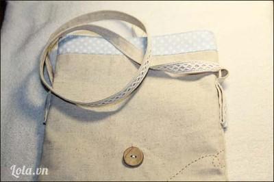 Cuối cùng bạn may một ống vải nhỏ làm quai túi, may đè ruy-băng ren lên một mặt ống vải bóp bẹp là phẳng đề trang trí cho quai thêm nét handmade. Đính hai đầu quai vào hai bên đầu sườn túi, cách đều mép túi 5c - 10cm. Nhấc quai túi lên, thấy miệng túi gấp xuống tới đâu thì đính cúc gỗ tới đó.
