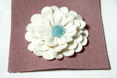 Khâu một hình tròn nhỏ bằng vải dạ xanh hoặc vàng làm nhị hoa, đồng thời sẽ che đi phần khâu chân cánh.