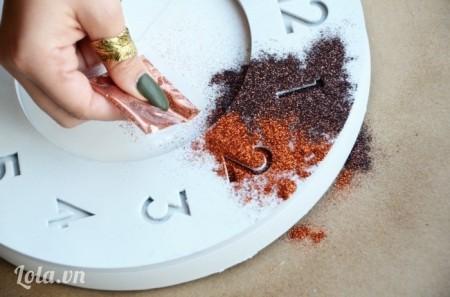 Bước 3:  Rắc bột nhũ từng màu một vào chỗ vừa xịt keo.