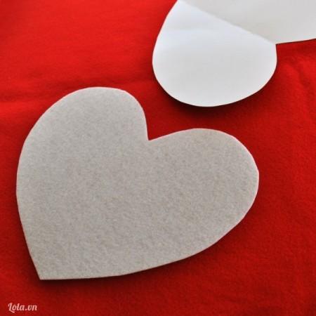 Cắt một hình trái tim từ mảnh vải nỉ mềm trắng với kích thước tùy ý để trang trí vỏ gối handmade. Để hình trái tim trang trí gối handmade được cân đối, bạn nên cắt một hình trái tim từ giấy với kích cỡ y hệt, sau đó ghim vào mảnh vải dạ nỉ trắng rồi cắt theo.