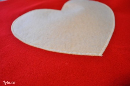 Gắn hình trái tim từ vải nỉ trắng vào chính chữa miếng vải dạ nỉ hàn quốc đỏ làm vỏ gối, sau đó dùng kim khâu hay máy vắt sổ khâu xung quanh viền trái tim. Vậy là bạn đã hoàn thành mặt trước của món quà tặng người yêu rồi
