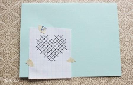 Phác thảo hình trái tim cross-stitch lên giấy ô li nhỏ hoặc vải aida, rồi dùng băng dính dán hờ lên vị trí bạn muốn thêu chữ thập trên tấm thiệp.