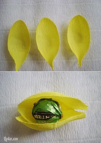 Bước 2:- Vì giấy nhún có độ co giãn tốt, bạn dùng tay kéo nhẹ hai bên tạo độ cong cho 6 cánh hoa.- Đặt 3 cánh hoa chồng lên nhau, dán mép cánh hoa giữa chồng trên mép hai cánh hoa hai bên và đặt viên kẹo vào trong.