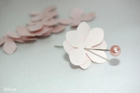 Dùng keo nến gắn ngọc trai lên đầu mỗi cây kim, đặt hai cánh hoa so le, xâu kim có gắn ngọc qua mỗi bông hoa ghép.