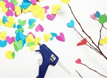 Bước 2:  Sau đó, bạn dùng súng bắn keo dán các hình trái tim rải khắp các cành cây khô trông cho tự nhiên. Không nên dán quá nhiều sẽ làm rối mắt nha các ấy.