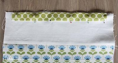 Gấp 2 biên vải của mảnh vải may viền rút, may cả 2 mảnh vải.  - Gấp đôi theo chiều ngang mảnh vải, là phẳng.  - Ghim cố định vải may viền vào mặt phải của mặt trước túi.  - Làm tương tự với mặt lưng của vải.