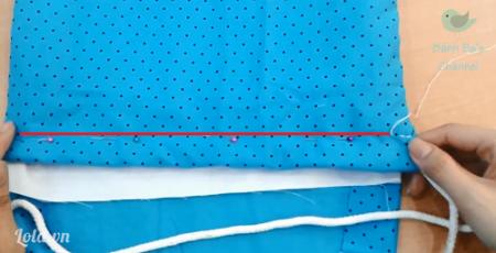 Dùng mũi đột mau khâu qua cả 2 lớp vải. Vì lớp vải khá dày nên trước khi khâu, bạn nên dùng ghim để cố định lại lớp vải.