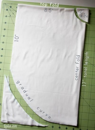 - Gập tiếp mảnh vải ở trên lại theo chiều rộng của áo.- Ở góc gập vải, bạn cắt 1 vòng lượn có bán kính khoảng 5 - 6cm.- Ở mép vải chiều dài áo, bạn đo từ mép trên xuống 25,4cm, đánh dấu điểm này lại rồi vẽ đường vòng cung từ đây sang đến mép vải bên kia.