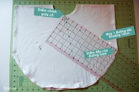 - Từ điểm chính giữa của cổ áo, bạn vẽ 1 đường chéo đến điểm đầu của đường lượn ở 2 mép vải. Sau đó, may cố định 1 đường khoảng 10cm trên đường vẽ đó, tính từ mép ngoài của vải vào.