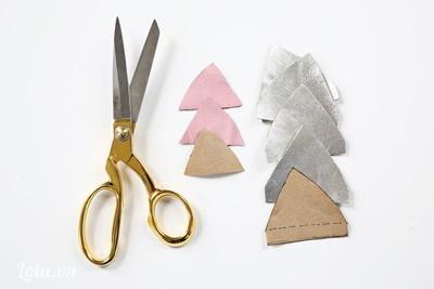 - Cắt 4 miếng vải tam giác màu bạc làm tai mèo kích thước 8cm (cạnh đáy) x 5cm (chiều cao)   2,6cm ở đáy. Cắt 2 miếng vải tam giác màu hồng nhỏ hơn miếng vải tam giác trên để làm phần trong của tai.